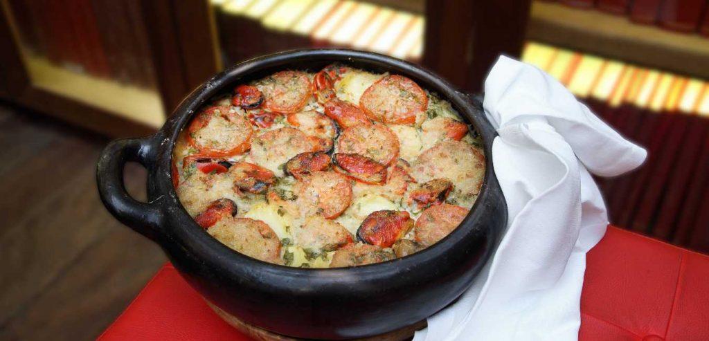 tiella noir avec plat cuisiné de pommes de terre, tomates, riz et moules